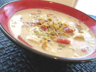 A bowl of creamy chicken enchilada soup topped with crushed tortilla chips.