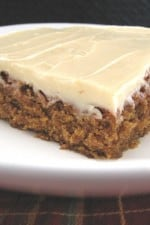 A slice of gingerbread bar topped with cream cheese frosting.