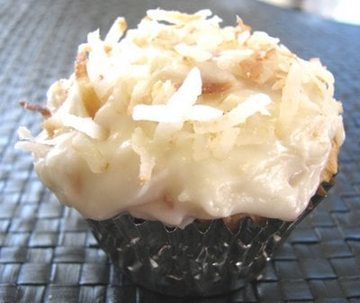 A Coconut Cupcake topped with toasted coconut and cream cheese frosting.
