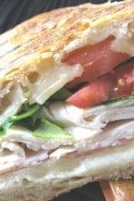 A crispy chicken, artichoke, swiss, and prosciutto panini in a crusty roll