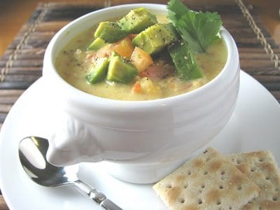 A bowl of chicken corn chowder topped with creamy avocado served with crackers on the side