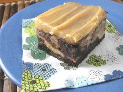 Caramelized Roasted Banana Brownies with Peanut Butter Sweet Cream Frosting on top. The brownie is sitting atop a flower-decorated napkin on a blue plate.