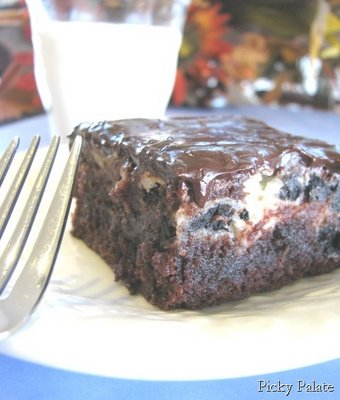 A piece of Cookies and Cream Brownies topped with a Chocolate Peanut Butter Ganache next to a fork and a glass of milk.