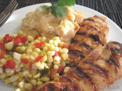 A plate of Sweet Sautéed Corn, Smoky Mashed Potatoes, and Adobo Peach BBQ Chicken.