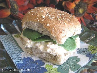 An Easy Tuna Fish Sandwich served on a whole wheat roll with fresh spinach.