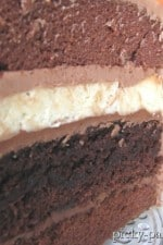 A close up of Double Chocolate Cheesecake Layer Cake showing the layers of chocolate cake, frosting, cheesecake, and brownie.