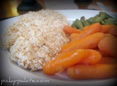 A plate full of Crispy Cashew Coconut Tilapia with Honey Glazed Carrots and Garlic Seasoned Green Beans.