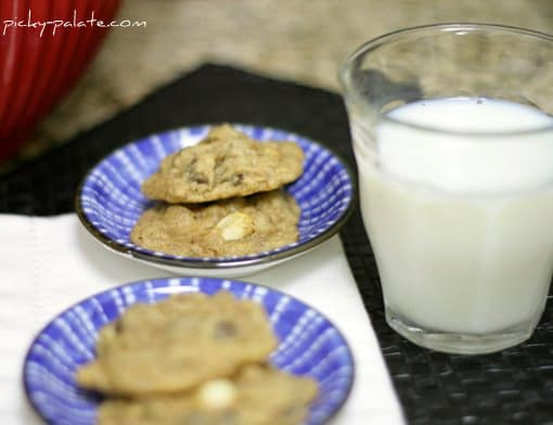 Two plates each with two Caramel Apple Chocolate Chip Cookies next to a glass of milk