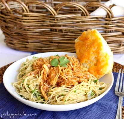 A Bowl of BBQ Chicken Spaghetti with a Piece of Cornbread in Front of a Wicker Basket