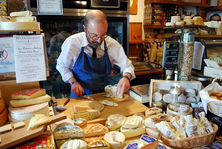 A Man in a Blue Apron Behind the Counter of the Cheese Store