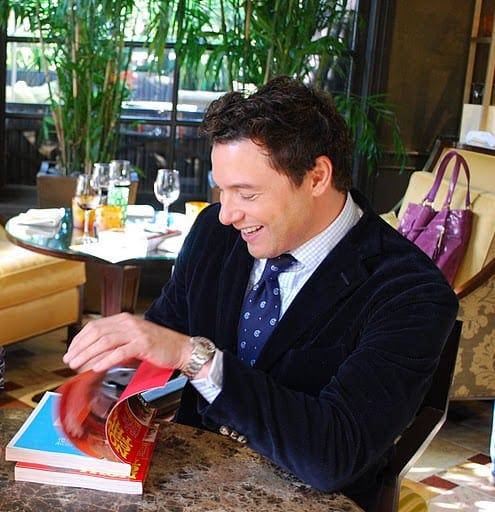 Rocco DiSpirito Smiling While Flipping Through His Cookbook