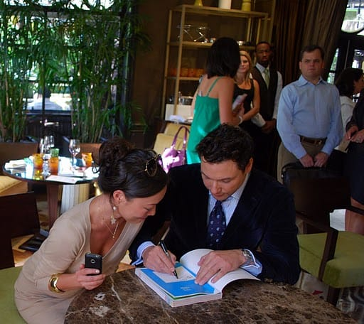 Sarah and Rocco Looking at Rocco's Cookbook as He Signs It