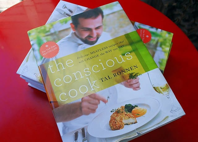 A Copy of The Conscious Cook by Tal Ronnen on a Small Red Table