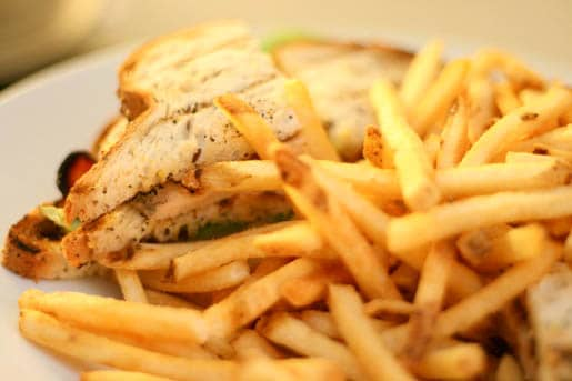 A Chicken Club Sandwich on a Plate with Fries