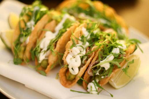 Five Lobster Tacos on a Plate with Lime Slices
