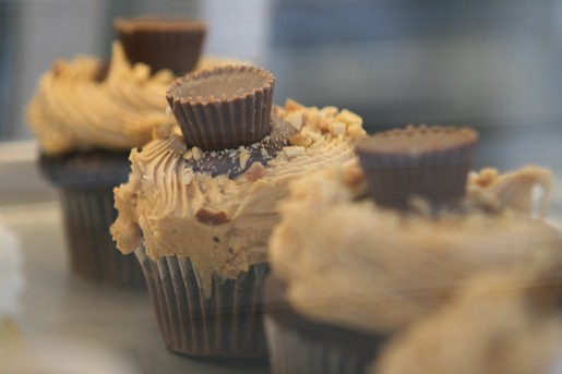 Four Chocolate and Peanut Butter Cup Cupcakes Arranged in a Line