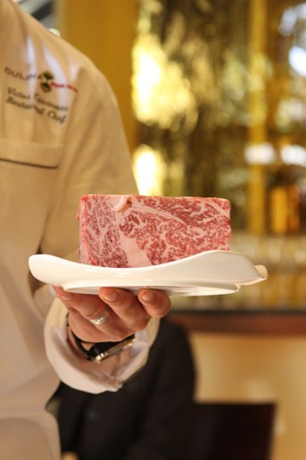 A Slab of Kobe Beef on a Fancy White Plate Being Held by Chef Victor