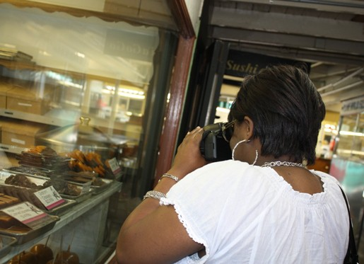 Shelisa Photographing a Display of Various Baked Goods