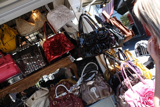 A Bunch of Colorful Bags and Handbags at a Purse Kiosk