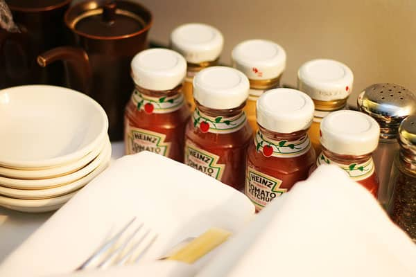 Heins Ketchup and Mustard Bottles Beside a Stack of Five Bowls