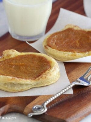 Two Cinnamon Toasted Pumpkin Pie Tarts with a fork and a glass of milk.