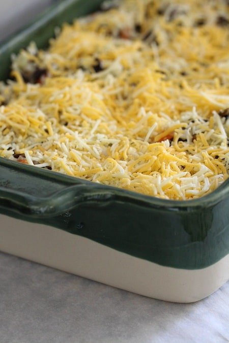 topping chicken and rice casserole with cheese
