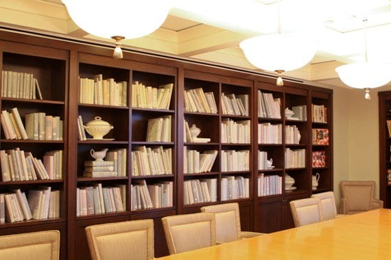 A Large Bookshelf Behind a Long Wooden Dining Table