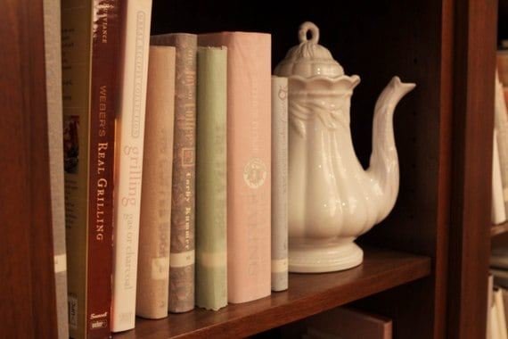 A Close-Up of Books and a Tea Kettle on a Dark Wooden Shelf