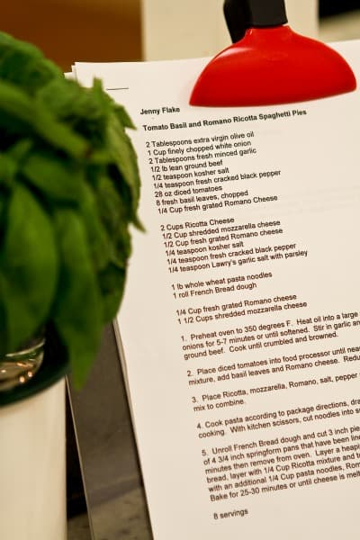 Jenny's Spaghetti Pies Recipe on a Clipboard Next to a Potted Plant