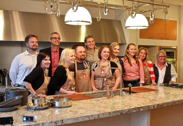 A Group Photo of the Cook-Off Judges, PR People and Contestants Behind a Counter