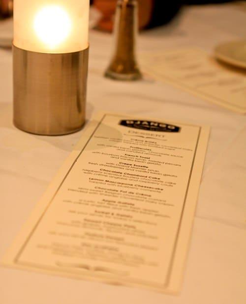 A Close-Up Image of the D'Jango Dinner Menu Next to a Candle