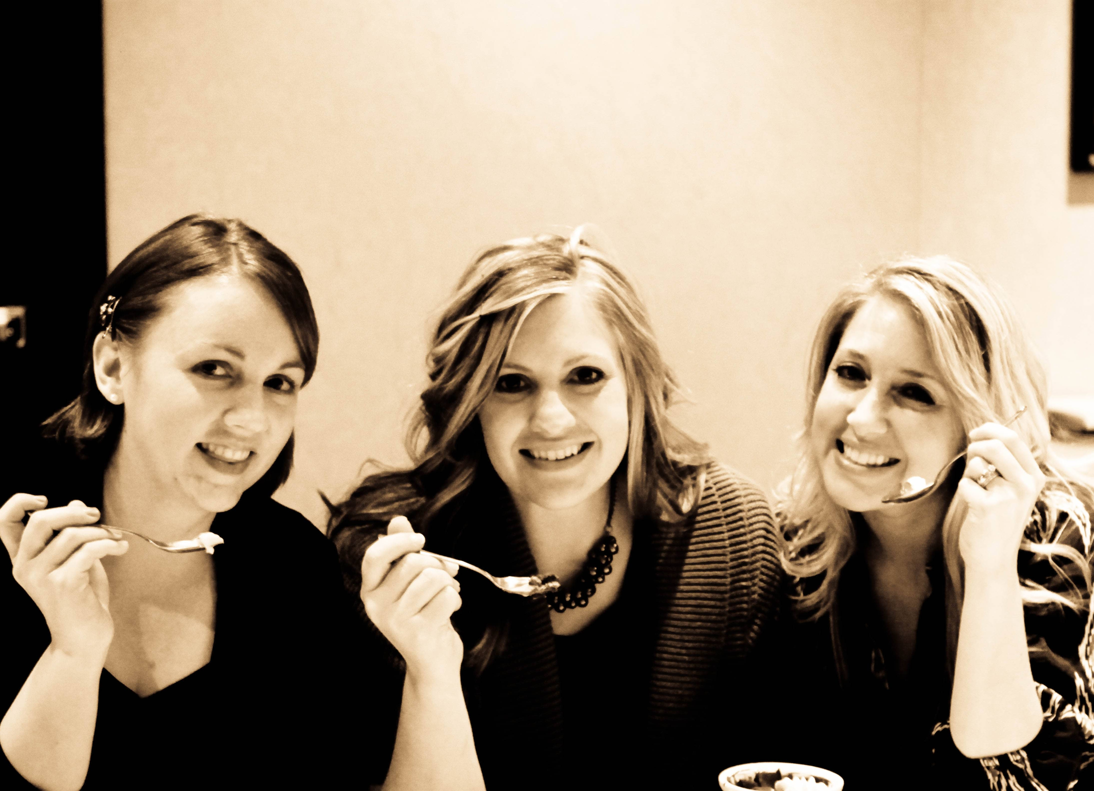A Sepia Image of Three Food Bloggers Posing with Full Spoons