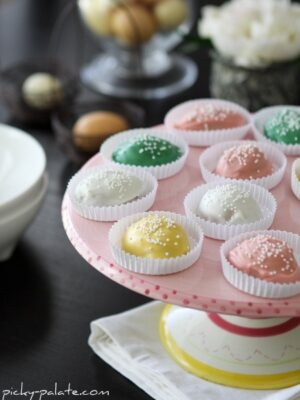 A platter full of pastel-colored homemade Chocolate Covered Peanut Butter Eggs in white wrappers.