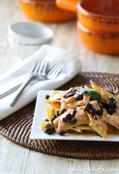 Creamy Salsa and Black Bean Nachos on a Plate with Two Forks