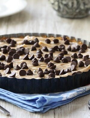 A Creamy Peanut Butter Chocolate Chip Tart with a fork and knife.