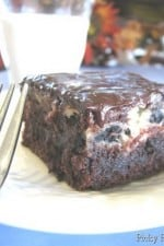 A Cookies and Cream Swirled Brownie topped with a Chocolate and Peanut Butter Ganache with a fork and glass of milk.