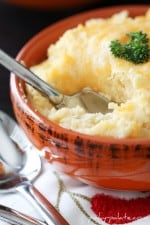 A Spoon Digging into a Bowl of Smoky & Cheesy Buttermilk Baked Mashed Potatoes