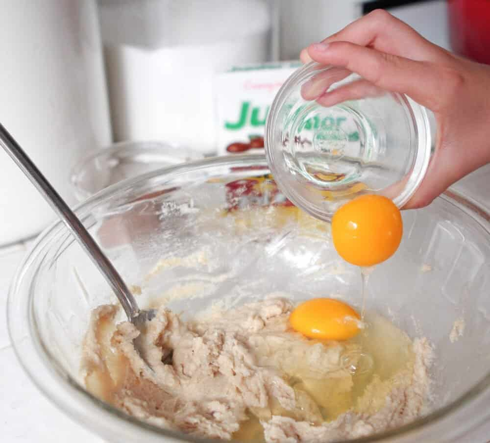 adding eggs to mixing bowl for chocolate cookie recipe