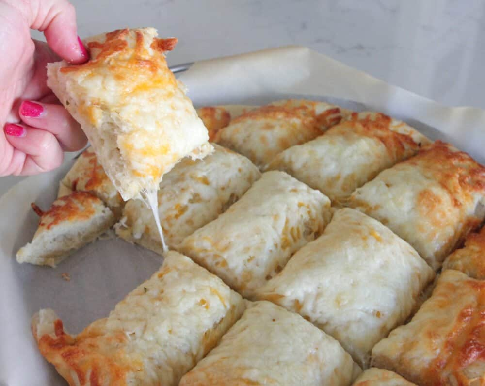 showing cheese pull of pizza bread