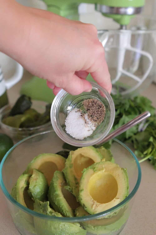 adding seasonings to bowl of avocados