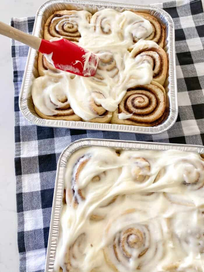 adding frosting to cinnamon rolls