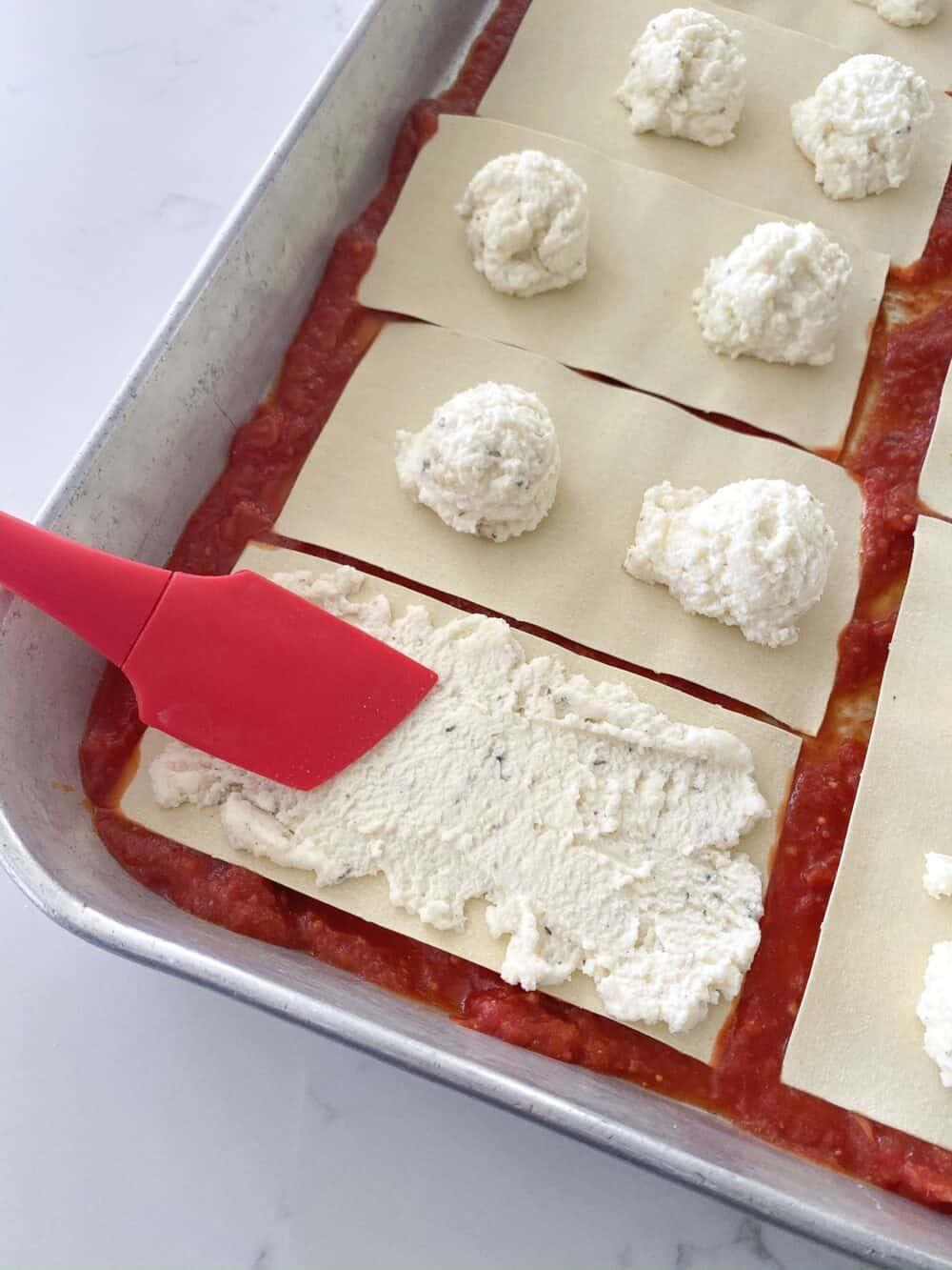 spreading ricotta layer for easy lasagna recipe