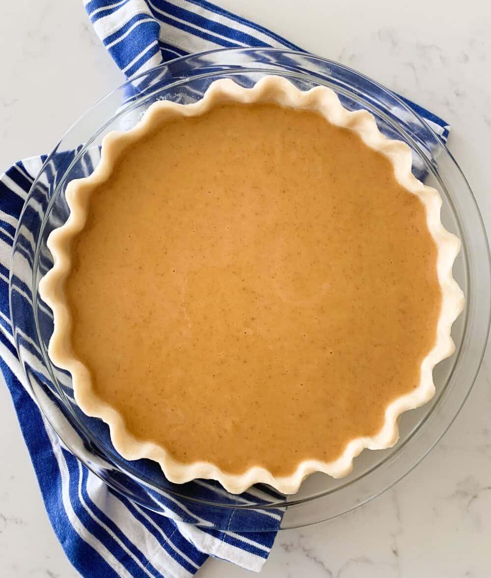 pumpkin pie filling in pie crust ready to bake