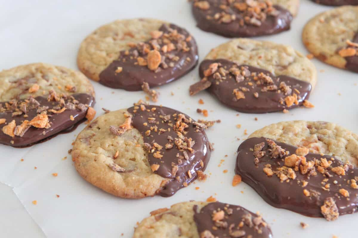 dipped butterfinger cookies on parchment paper