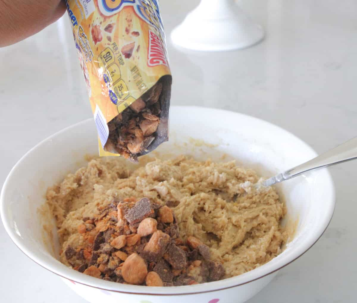pouring butterfinger pieces into cookie dough bowl