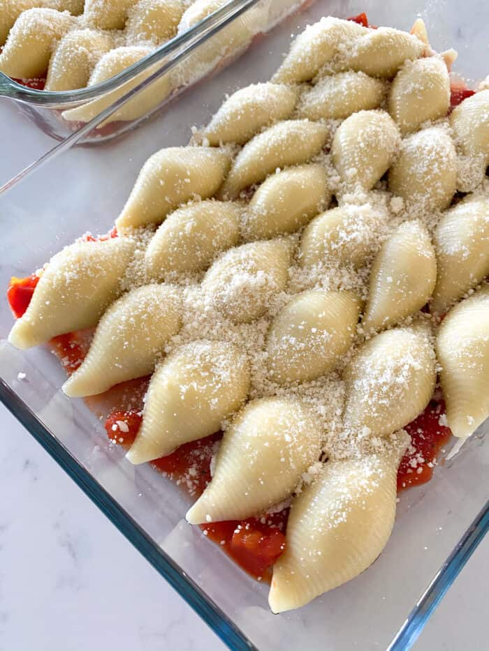 stuffed shells in a baking dish with parmesan
