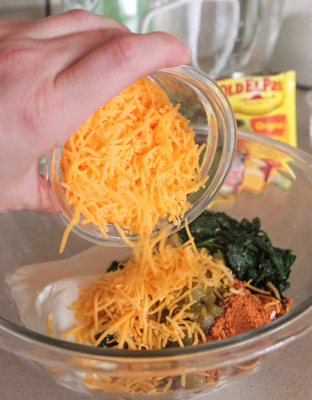 adding shredded cheese to mixing bowl