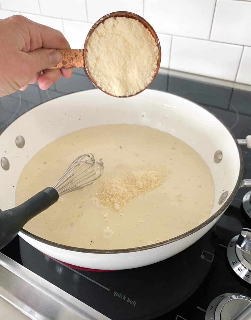 adding parmesan cheese to sauce of chicken spaghetti
