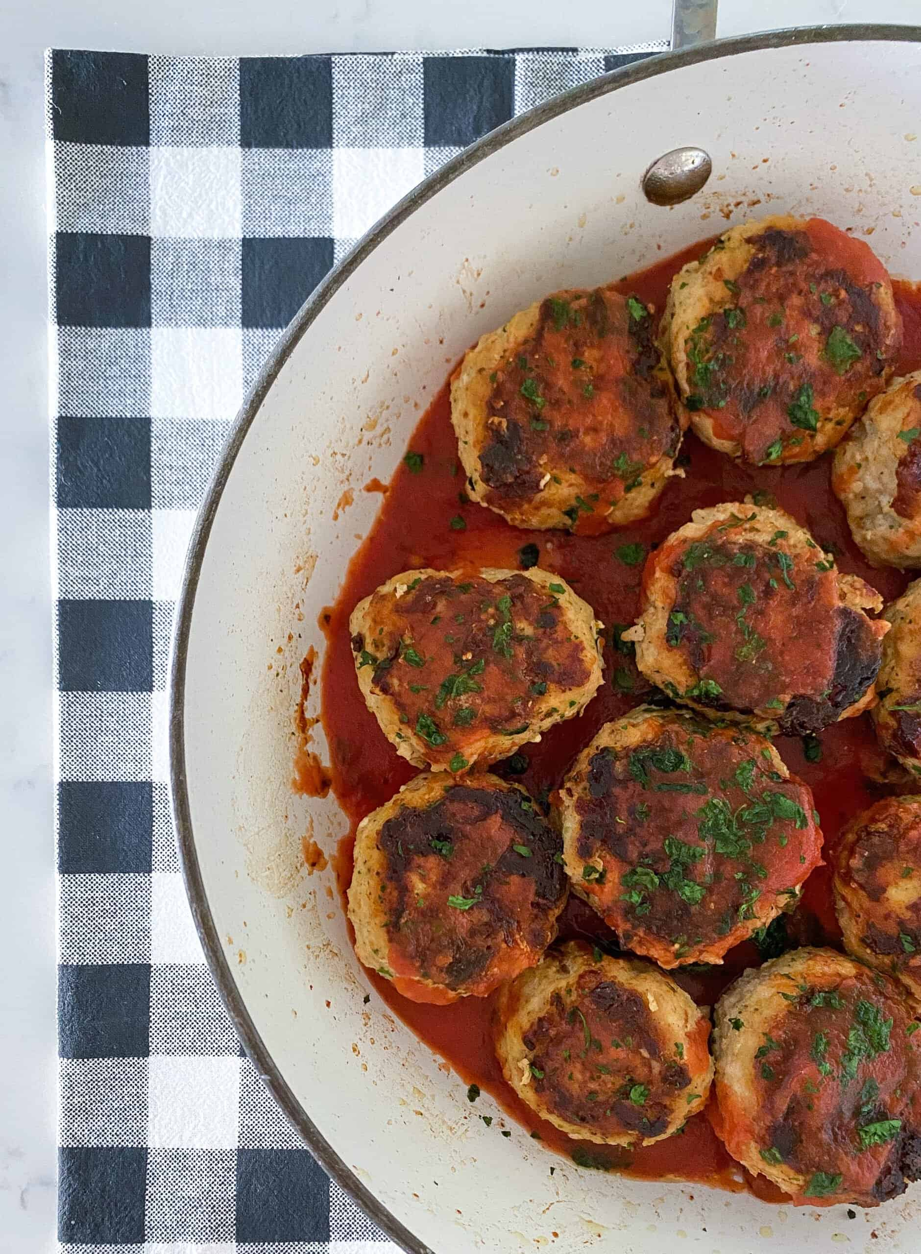 A bowl full of ground chicken meatballs in sauce