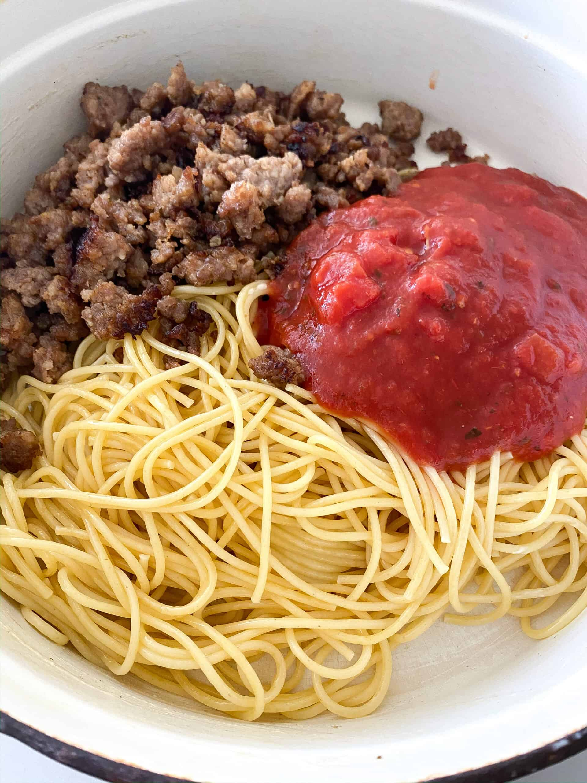 red sauce over browned sausage in bowl